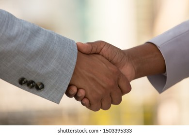 Closeup of business colleagues handshake. Business people greeting each other outside. Agreement concept