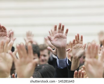 Closeup of business crowd raising hands