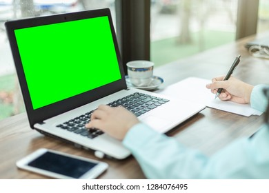 Close-up of business female working with laptop make a note in coffee shop like the background.green screen