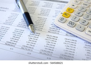 Closeup of business financial statement position reports with pen and calculator