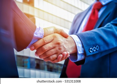 closeup business handshake on building background