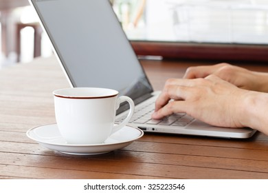 Closeup of business man hand typing on laptop keyboard and coffee
