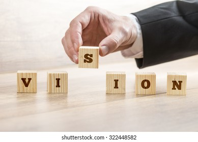 Closeup of business manager assembling a word Vision with six wooden cubes. Conceptual of business innovation and start up.