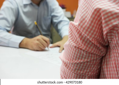 Close-up of business meeting, Two businessmen discussing a deal, signing a contract on white table, with close up waiting person and the far blurred decision-makers person in the orange wall painted