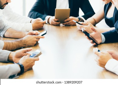 Close-up of business men and woman all using their phone on desk inside office space