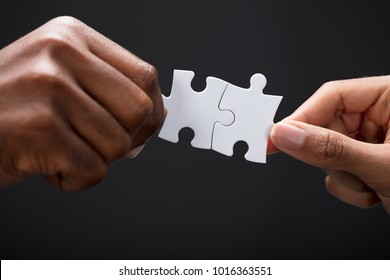 Close-up Of Business Partners Combining Two White Puzzle Pieces On Black Background