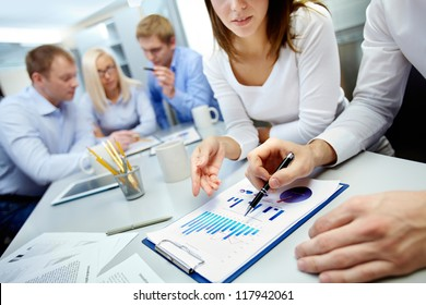 Close-up of business partners hands over document with their colleagues working on background
