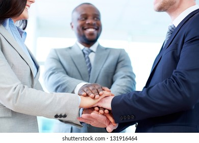 Close-up of business partners making pile of hands
