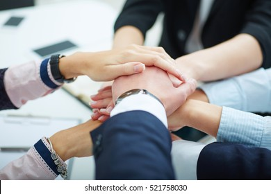 Close-up of business partners making pile of hands at meeting.