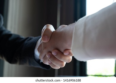 Close-up  of business partners shaking hands andhand business men and women who shaking hands.