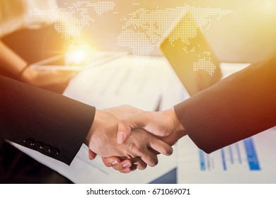 Closeup of business people handshake greeting deal of world global international trade and export concept with world global cartography globalization, business people finishing up a meeting.