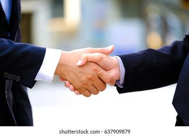Closeup of business people handshake meeting concept. Image businessmans handshake. Successful businessmen handshaking after good deal. Horizontal, blurred background.