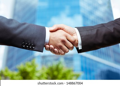 Close-up of business people handshaking on background of modern building