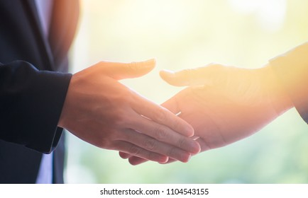 Close-up Business people shaking hands, finishing up meeting. greeting and partner in sun light