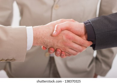 Close-up of business people`s arms handshaking. Against the background of a man in a suit.
