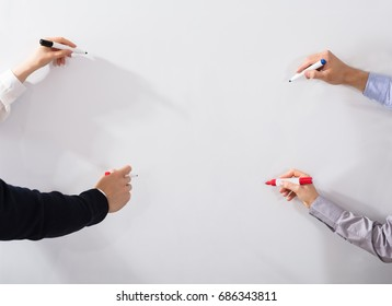 Close-up Of Business People's Hands Holding Different Marker Writing On Whiteboard