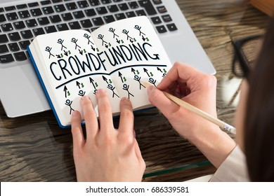 Close-up Of A Business Person Drawing Crowdfunding Chart On Notebook Over The Laptop