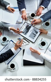 Close-up of business team hands over papers during discussion of a new project