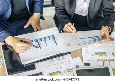Close-up of business team using pen with financial diagram and digital tablet