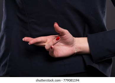 Closeup of business woman with crossed fingers behind her back as falsehood concept