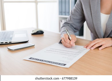 closeup of business woman decided retired from company and writing personal resignation letter explaining plan in future to application leaving.