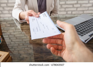 Close-up Of A Business Woman Giving Cheque To Her Colleague At Workplace In Office