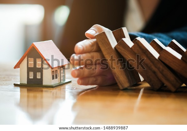Close-up Of Business Woman Hand Stopping and Covering The Wooden Blocks From Falling On House Model, insurance concept.