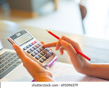 Closeup business woman hand using a calculator with red pencil in cafe office. Business finance and education concept.