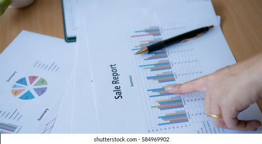 Close-up of Business woman hands pointing at turnover graph while discussing it on wooden desk, Business financial working concept