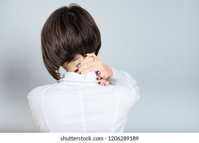 Closeup of business woman with neck pain, short hair cutting, isolated over gray background