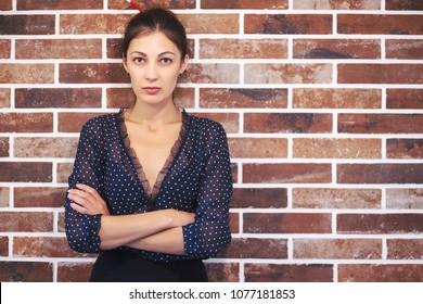 Close-up business woman portrait. Portrait of attractive woman wearing blue blouse with white dots on a brick background with copy space available.
