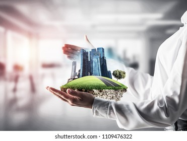 Closeup of business woman in shirt keeping green island with skycraper city in her hands with office view and sunlight on background. Mixed media.