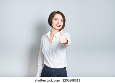 Closeup of business woman showing thumbs up, like it, short hair cut, isolated over gray background