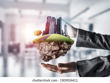 Closeup of business woman in suit keeping green island with skycraper city in her hands with sunlight and office view on background. Mixed media.