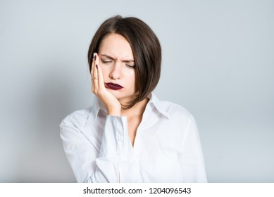 Closeup of business woman with toothache, short hair cut, isolated over gray background