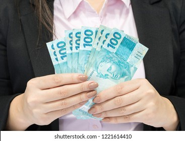Close-up business woman wearing suit holding brazilian money notes. Brazil one hundred (100) reais. Selective focus.
