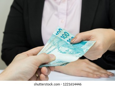 Close-up business woman wearing suit getting cash from brazilian money notes. Brazil one hundred (100) reais. Selective focus.