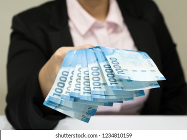 Close-up business woman wearing suit holding chilean money notes. Chile ten thousand (10000) pesos. Selective focus.