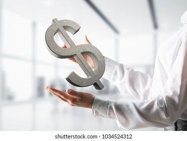 Closeup of business woman in white shirt keeping stone dollar sign in hands with office view on background. Mixed media.