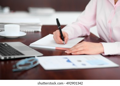 Closeup of a business woman writing in a notebook