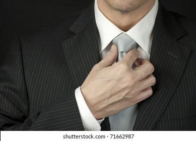 Close-up of a businessman adjusting his tie.
