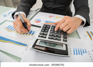 Close-up Of Businessman Analyzing Graph And Using Calculator