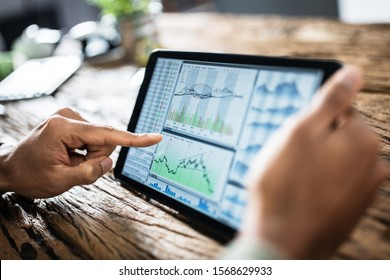 Close-up Of Businessman Analyzing Stock Market Status On Digital Tablet