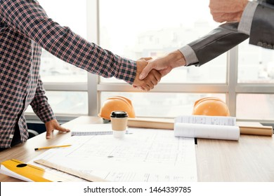 Close-up of businessman and architect standing and shaking hands to each other after successful discussion of new project at meeting at office