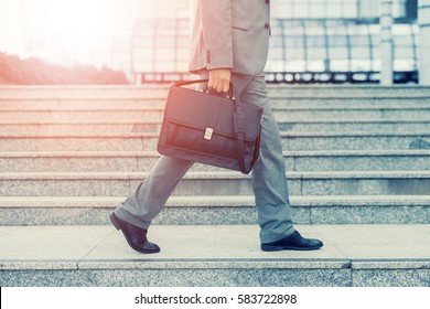 Close-up of businessman with a briefcase running in a city street.Hurrying to work.