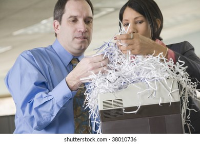 Close-up of a businessman and a businesswoman looking at shredded papers