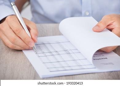 Closeup of businessman calculating accounts at desk