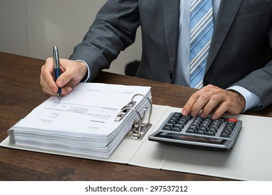 Close-up Of Businessman Calculating Bills With Calculator In Office