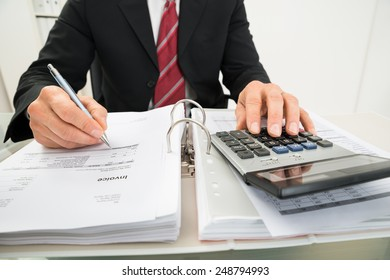 Close-up Of A Businessman Calculating Invoice At Office Desk