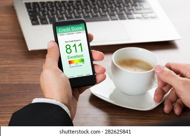 Close-up Of A Businessman Checking Credit Score Online On Cellphone While Having Coffee